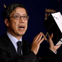 Kazuyoshi Umemoto, Japan's chief negotiator for the Trans-Pacific Partnership, holds up a copy of the original TPP deal as he speaks at a news conference Tuesday at the Foreign Correspondents' Club of Japan in Tokyo. | REUTERS