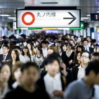 Commuters hurry at Ikebukuro Station in Tokyo. | GETTY IMAGES