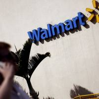 A man talks on his mobile phone in front of a Walmart store in Sao Paulo in 2016. | REUTERS