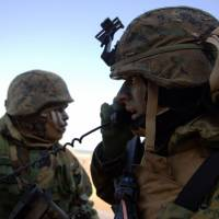 U.S. Marines listen to radio commands during the annual joint exercises with the South Korea military west of Seoul in March 2003. | BLOOMBERG