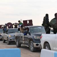 A picture taken Tuesday shows a convoy of pro-Syrian government fighters arriving in Syria's northern region of Afrin. Kurdish forces said in a statement that pro-regime fighters deployed to Afrin will take up positions and 'participate in defending the territorial unity of Syria and its borders,' countering Turkey's offensive on the area. | AFP-JIJI