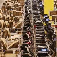 Boxes of goods pass along an automated conveyor belt system at Amazon's new fulfillment center in Kolbaskowo, Poland, on Friday. | BLOOMBERG
