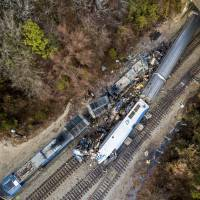 The early morning crash Sunday between an Amtrak train (bottom right) and a CSX freight train is seen in Cayce, South Carolina. The Amtrak passenger train slammed into a freight train in the early morning darkness Sunday, killing at least two Amtrak crew members and injuring more than 110 people, authorities said. | AP