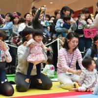 Mothers and their babies take part in a crawling competition at an event in Yokohama, Kanagawa Prefecture, in November 2015. | AFP-JIJI