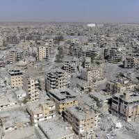 This Oct. 19 image from drone video shows damaged buildings in Raqqa, Syria, two days after Syrian Democratic Forces said military operations to oust the Islamic State group ended. A U.S. military official says the American-backed Syrian Democratic Forces in January  captured two notorious British members of an Islamic State insurgent cell commonly dubbed 'The Beatles' and known for beheading hostages. | AP