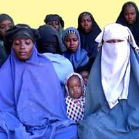 This photo made from a video released by the Islamist militant group Boko Haram on Jan. 15 shows at least 14 of the schoolgirls abducted from the northeast Nigerian town of Chibok in April 2014. | AFP-JIJI