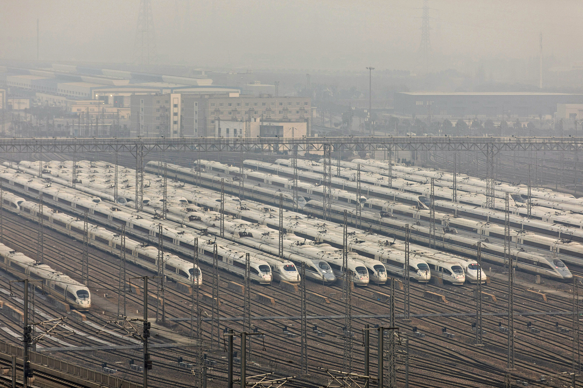 High-speed bullet trains operated by China Railway Corp. sit in a train yard shrouded in haze on the outskirts of Shanghai on Thursday.   BLOOMBERG