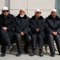 Men wait for afternoon prayers to begin at a mosque in Linxia, in China's Gansu province, home to a large population of ethnic minority Hui Muslims, on Feb. 1. | REUTERS