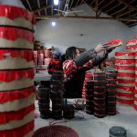 A worker prepares pyrotechnic products at Liuyang Standard Fireworks Manufactory in Liuyang, China, on Jan. 29.   REUTERS