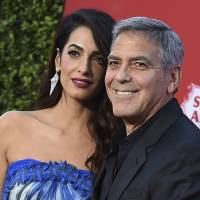 Amal Clooney and George Clooney arrive at the premiere of 'Suburbicon' in Los Angeles in October. George and Amal Clooney are donating $500,000 to students organizing nationwide marches against gun violence, and they say they'll also attend next month's planned protests. | JORDAN STRAUSS / INVISION / VIA AP