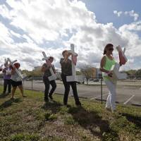 Volunteers help carry 17 crosses to be placed outside the Marjory Stoneman Douglas High School in Parkland, Florida, Sunday, where 17 people were killed in a mass shooting on Wednesday. Nikolas Cruz, a former student, was charged with 17 counts of premeditated murder. | AP