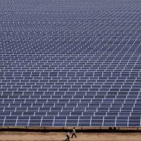 Workers walk past solar panels at the Gujarat Solar Park in Charanka in the Patan district of India in this file photo. | AP