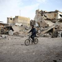 A young man rides bicycle near damaged houses in the besieged town of Douma, eastern Ghouta, Damascus, Monday. | REUTERS