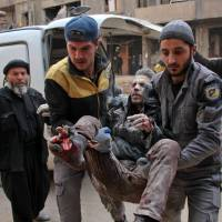 Civil Defense volunteers, known as the White Helmets, carry a wounded man into a makeshift hospital in the rebel-held town of Douma, following airstrikes by regime forces on the besieged eastern Ghouta region on the outskirts of the capital Damascus on Monday. Regime airstrikes have pushed the death toll from three days of bombing in Syria's rebel Ghouta to over 200 as Damascus pitched pro-government forces into the fray against Turkey in a Kurdish-held border region. | AFP-JIJI