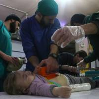 Syrian medics tend to a baby at a makeshift clinic following Syrian government bombardments in Douma, in the besieged eastern Ghouta region on the outskirts of the capital Damascus, on Thursday. The baby died. | AFP-JIJI