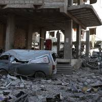 A picture taken Wednesday shows a damaged make-shift ambulance vehicle among rubble in a heavily damaged street in the rebel-held enclave of Hamouria in eastern Ghouta near Damascus, following a reported regime airstrike.   AFP-JIJI