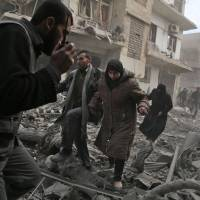 A Syrian civil defense member speaks on a wireless transmitter as other civilians flee an area hit by a reported regime airstrike in the rebel-held town of Saqba, in the besieged Eastern Ghouta region on the outskirts of Damascus on Tuesday. | AFP-JIJI