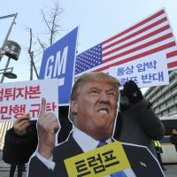 South Koreans protest GM Korea's restructuring near the U.S. Embassy in Seoul on Tuesday. The signs read, 'We oppose Trump's trade pressure and denounced GM's brutality.' | AP