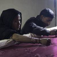 Mohammud Sanu and his wife work on fine needlework by the light of a solar lamp in Pipargaon Nevada, a village in the Indian state of Uttar Pradesh, on Jan. 9.   THOMSON REUTERS FOUNDATION