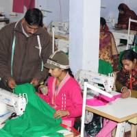 Mohammad Riyaz, who set up a solar-powered garment manufacturing unit in the village of Kamlapur in Uttar Pradesh, works with one of the 25 women stitching clothing on Jan. 9.   THOMSON REUTERS FOUNDATION