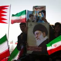 Demonstrators wave Iranian and Bahraini flags as they hold pictures of Supreme Leader Ayatollah Ali Khamenei during a ceremony to mark the 33rd anniversary of the Islamic Revolution, in Tehran's Azadi square in February 2012. | REUTERS