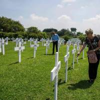 Family members pay their respects to the 915 Dutch soldiers killed in the Battle of the Java Sea at the Dutch war cemetery Ereveld in Surabaya on Tuesday. The ceremony marks the 76th anniversary of the Feb. 27, 1942, Battle of the Java Sea, where the Allied American-British-Dutch-Australian (ABDA) naval forces suffered defeat from the naval armada of Japanese invading forces during World War II. | AFP-JIJI