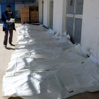 Bags containing the bodies of migrants who were killed in a truck crash are seen at a hospital in Bani Walid town, Libya, Wednesday. | REUTERS