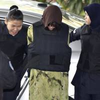 Vietnamese Doan Thi Huong, center, is escorted by police as she arrives for a court hearing in Shah Alam, Malaysia, on Feb. 9. Doan and Siti Aisyah of Indonesia have pleaded not guilty to killing Kim Jong Nam on Feb. 13, 2017, at a crowded Kuala Lumpur airport terminal. | AP