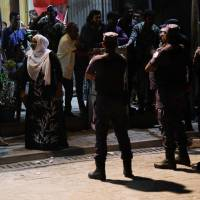 Security forces stand outside the Maldivian Democratic Party (MDP) office as they barricade it in Male on Wednesday. The Maldives president welcomed a Supreme Court move to reinstate the convictions of high-profile political prisoners after he arrested two top judges and declared a state of emergency, plunging the upmarket holiday paradise into chaos. | AFP-JIJI