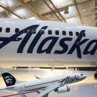 The new logo of Alaska Airlines is shown next to a model of a plane with the old livery in Seattle in 2016. An Alaska Airlines flight to Seattle was forced to return to Anchorage, Alaska, early Wednesday after a passenger locked himself in the bathroom, took off all his clothes and refused to follow crew instructions. | AP