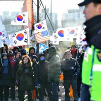 Protesters hold U.S. and South Korean flags as they protest against the unified Korea women's ice hockey team outside an ice rink before a friendly match between the combined team and Sweden in Incheon, South Korea, on Sunday ahead of the Pyeongchang 2018 Winter Olympics.   AFP-JIJI