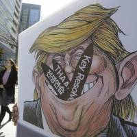 A woman walks by a poster with an illustration of U.S. President Donald Trump held by a protester during a rally to oppose a plan to deploy an advanced U.S. missile defense system called Terminal High Altitude Area Defense (THAAD) and joint military exercises between the U.S. and South Korea, near the U.S. Embassy in Seoul last March. | AP