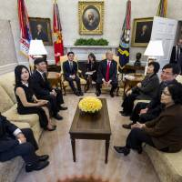 U.S. President Donald Trump and North Korean defector Ji Seong-ho (center left) listen during a meeting with other defectors in the Oval Office of the White House in Washington on Friday. | BLOOMBERG