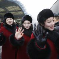 North Korean cheering squads wave upon their arrival at the Korean-transit office near the Demilitarized Zone in Paju, South Korea, on Wednesday. | POOL / VIA AP