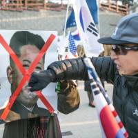 A demonstrator punches a portrait of North Korean leader Kim Jong Un during a protest outside Gangneung Arts Center ahead of the 2018 Pyeongchang Winter Olympics, in South Korea, on Feb. 8. | BLOOMBERG