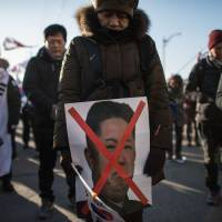 An anti-Pyongyang protester holds a picture of North Korean leader Kim Jong Un while others wave flags and shout slogans as a ferry carrying a North Korean art troupe for the Pyeongchang 2018 Winter Olympic Games approaches the South Korean port of Mukho on Tuesday. | AFP-JIJI