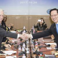U.S. Secretary of Defense Jim Mattis shakes hands with South Korean defense chief Song Young-moo ahead of a meeting in Seoul last October. | BLOOMBERG