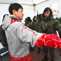South Korean soldiers inspect a visitor at a security checkpoint as they replace security guards showing symptoms of norovirus at the Gangneung Ice Arena in Gangneung on Tuesday. | AFP-JIJI