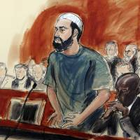 In this courtroom drawing, defendant Ahmad Khan Rahimi reads a statement to the judge during his sentencing hearing in New York Tuesday. Rahimi was sentenced to multiple terms of life in prison for setting off small bombs in two states, including a pressure cooker device that blasted shrapnel across a New York City block. At right is attorney Xavier Donaldson, Rahmin's attorney. | ELIZABETH WILLIAMS / VIA AP