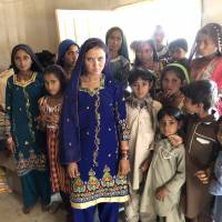 Women and children in the Pakistani village of Murid Khoso pose beside their prized battery hub on Dec. 26.   THOMSON REUTERS FOUNDATION / ZOFEEN EBRAHIM