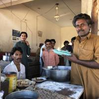 The chef at the Bhittai restaurant in Khorwah, Pakistan, holds up at plate of food on Dec. 26. The restaurant is lit by solar power.   THOMSON REUTERS FOUNDATION / ZOFEEN EBRAHIM