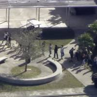 In this frame grab from video provided by WPLG-TV, students from the Marjory Stoneman Douglas High School in Parkland, Florida, evacuate the school following a shooting there on Wednesday. | WPLG-TV / VIA AP