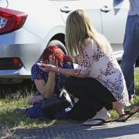 A woman consoles another as parents wait for news regarding a shooting at Marjory Stoneman Douglas High School in Parkland, Florida, Wednesday. A shooter opened fire at the Florida high school Wednesday, killing people, sending students running out into the streets and SWAT team members swarming in before authorities took the shooter into custody. | AP