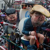 A carnival chariot is seen with figures of U.S. President Donald Trump and North Korean leader Kim Jong Un during a parade in Torres Vedras, Portugal, Sunday. | REUTERS
