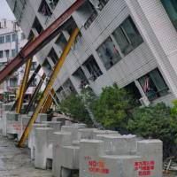A rescuer stands guard near a building supported by girders on Thursday in Hualien, Taiwan, after the city was hit by a 6.4 magnitude quake late on Tuesday. | AFP-JIJI