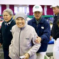 Ninety-one-year-old earthquake survivor Chen Shen-yin is escorted by volunteers at a detention center being used for displaced families on Thursday in Hualien, Taiwan. | AFP-JIJI