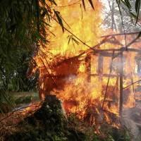 A house burns in Gawdu Tharya village near Maungdaw in Rakhine state in northern Myanmar in September. Aerial photos of Rohingya villages in Myanmar have emerged showing apparently bulldozed land with no recognizable signs of habitation, as activists say there are growing fears that the Muslim minority will lose not only their homes but their history. | AFP-JIJI