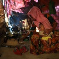 Hasina Khatun, 24, whose husband, Abdul Hashim, was among 10 Rohingya men killed by Myanmar security forces and Buddhist villagers on Sept. 2, cooks a meal at Thayingkhali camp in Cox's Bazar, Bangladesh, Jan. 19. | REUTERS