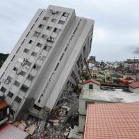 A rescue worker (bottom center) enters a quake-damaged hotel to look for survivors and bodies in Hualien, Taiwan, on Friday. | AFP-JIJI