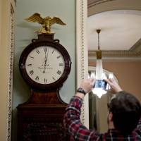 A man photographs the Ohio Clock after striking midnight at the U.S. Capitol in Washington early Friday. The Senate later passed a two-year budget agreement that would boost federal spending by $300 billion and suspend the debt ceiling for a year as lawmakers sought to end a partial government shutdown that began at midnight after Congress missed a funding deadline. | BLOOMBERG